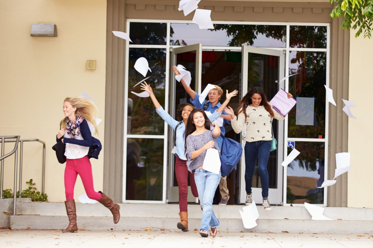 students running out of school throwing papers in the air