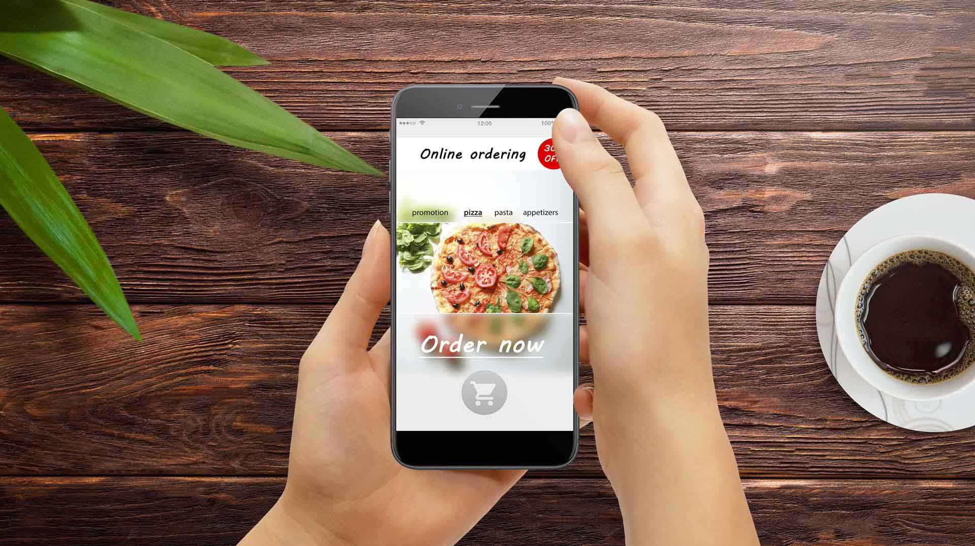Two hands holding a mobile phone that is displaying a pizza ordering application onscreen