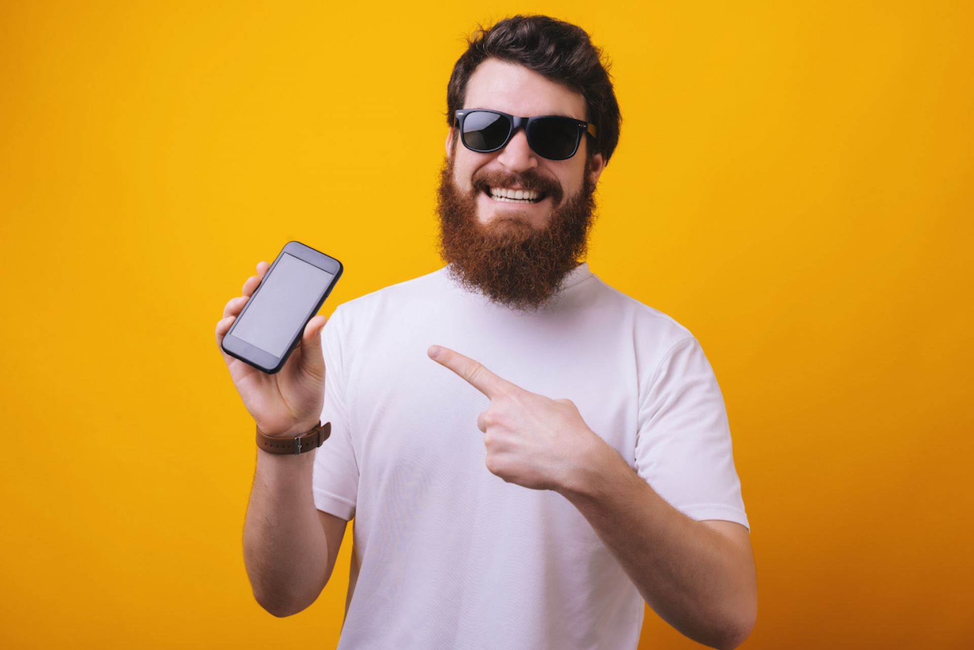Image of young brunette bearded man in sunglasses pointing finger on smartphone and smiling on camera
